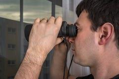 O homem está espiando seus vizinhos com binóculos fotos de stock
