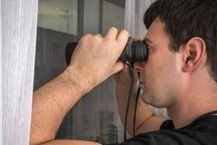 O homem está espiando seus vizinhos com binóculos fotografia de stock royalty free