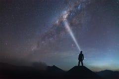 O homem está estando no monte e na luz até a Via Látea Fotos de Stock Royalty Free