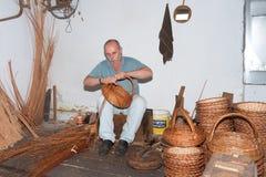 O homem está fazendo cestas de lingüeta em uma fábrica da trança em Madeira, Imagens de Stock
