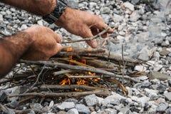 O homem está fazendo o fogo na natureza fotos de stock royalty free