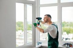 O homem está fazendo o reparo da janela fotografia de stock royalty free