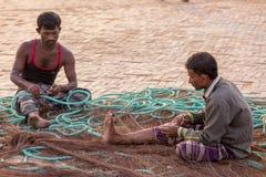 o homem 2 está fixando redes do barco lá de pesca Foto de Stock