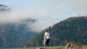O homem está girando a menina no vestido rústico redondo no prado no fundo das montanhas cobertas com filme