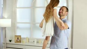 O homem está girando sua filha em uma sala video estoque