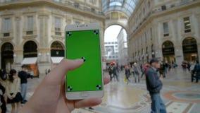 o homem está guardando o smartphone com galeria verde Vittorio Emanuele da tela II em Milão filme
