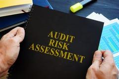 O homem está guardando o relatório de avaliação do risco de auditoria fotos de stock royalty free