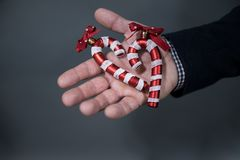 O homem está guardando um bastão de doces do brinquedo do Natal imagem de stock