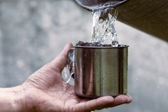 O homem está guardando uma caneca de aço e uma água boa está derramando de uma cubeta imagem de stock royalty free