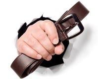 O homem está guardarando a correia em seus dedos através de um furo Imagens de Stock