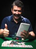 O homem está jogando o pôquer com a tabuleta em linha Jogador de cartão emocional foto de stock royalty free