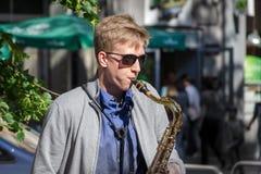 O homem está jogando o saxofone na rua Fotografia de Stock