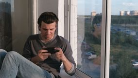 O homem está jogando um jogo no telefone celular que senta-se no balcão no por do sol filme
