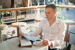 O homem está lendo um jornal em um café da rua no almoço foto de stock