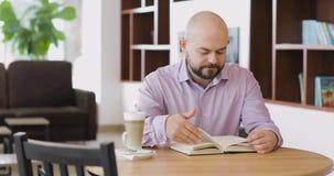 O homem está lendo um livro que senta-se no café do salão do hotel com o copo do cappuccino video estoque