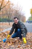 O homem está limpando as folhas caídas no parque do outono imagem de stock