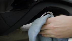 O homem está limpando, limpeza e está lustrando pelas tubulações de exaustão do cromo de pano do automóvel moderno, close-up video estoque
