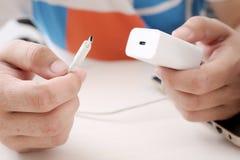 O homem está mantendo o adaptador e o cabo de USB disponivéis foto de stock