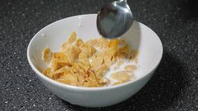 O homem está misturando flocos de milho e leite na bacia com a colher e está comendo-os para o café da manhã filme