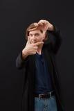 O homem está moldando com suas mãos Os homens olham através do quadro dos dedos Fotos de Stock