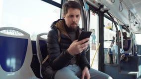 O homem está montando o ônibus e está olhando na tela do smartphone vídeos de arquivo