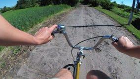 O homem está montando uma bicicleta em uma estrada rural na vila Vista da caixa na roda vídeos de arquivo
