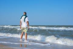 O homem está na praia na ressaca Fotografia de Stock Royalty Free