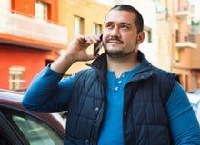 O homem está na rua e na fala no smartphone Foto de Stock Royalty Free