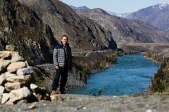 O homem está no banco de rio de Katun nas montanhas de Altai fotos de stock