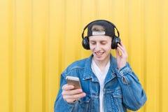 O homem está no fundo de uma parede amarela que escuta a música em fones de ouvido sem fio e na música de comutação imagem de stock royalty free
