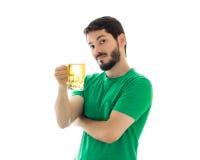 O homem está oferecendo uma caneca de ataúde Roupa verde vestindo Fotografia de Stock Royalty Free