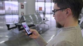 O homem está olhando o catálogo da loja de roupa em linha no smartphone vídeos de arquivo