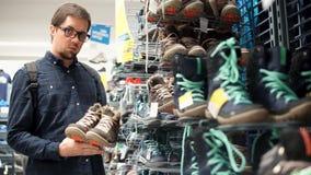 O homem está olhando com a admiração em um par das sapatas masculinas andando em uma loja filme