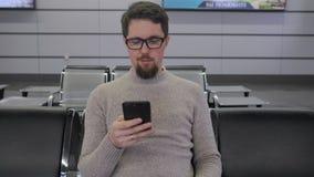 O homem está olhando na tela do smartphone vídeos de arquivo