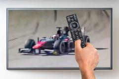 O homem está olhando o Fórmula 1 competir na tevê imagens de stock