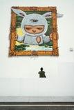 O homem está olhando a pintura na parede na galeria exterior Fotografia de Stock Royalty Free