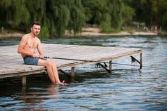 O homem está pescando com uma vara de pesca em suas mãos Fotos de Stock