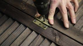 O homem está prendendo a dobradiça de porta ao detalhe da mobília que usa a broca elétrica vídeos de arquivo
