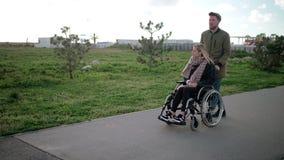 O homem está rolando a cadeira de rodas com a mulher loura nova, andando junto no parque filme