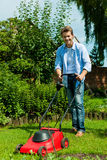 O homem está segando o gramado no verão fotos de stock royalty free