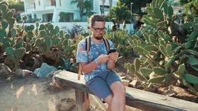 O homem está sentando-se em um banco no parque do jardim na noite ensolarada, usando o smartphone vídeos de arquivo