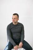 O homem está sentando-se em uma cadeira perto da parede branca imagens de stock royalty free