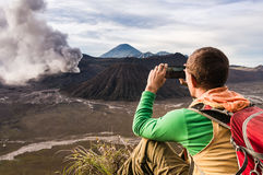 O homem está sentando-se no monte e está fazendo-se uma foto em seu smartphone Imagens de Stock Royalty Free