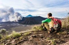 O homem está sentando-se no monte e está olhando-se na erupção do vulcão de Bromo Fotos de Stock