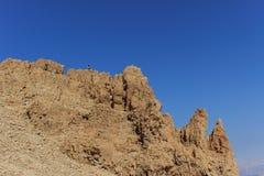 O homem está sentando-se sobre a montanha e está apreciando-se a paisagem do Mar Morto Fotografia de Stock Royalty Free