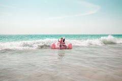 O homem está tendo o divertimento no flutuador inflável da associação do flamingo do rosa imagem de stock