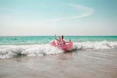 O homem está tendo o divertimento no flutuador inflável da associação do flamingo do rosa foto de stock royalty free