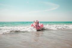 O homem está tendo o divertimento no flutuador inflável da associação do flamingo do rosa fotografia de stock royalty free