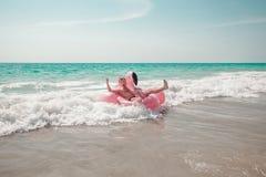 O homem está tendo o divertimento no flutuador inflável da associação do flamingo do rosa fotos de stock royalty free