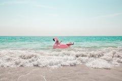 O homem está tendo o divertimento no flutuador inflável da associação do flamingo do rosa imagem de stock royalty free